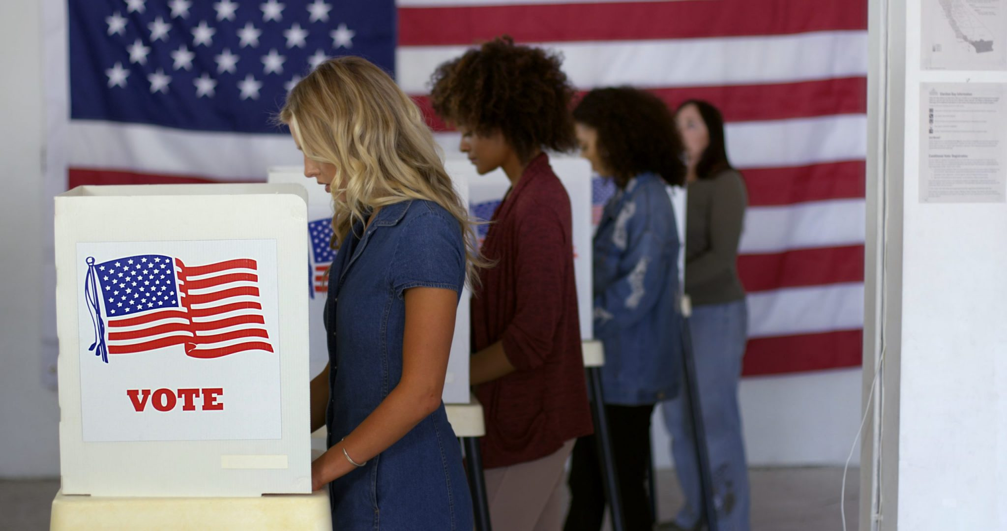Four women of various demographics filling in ballots and casting votes in booths at polling station, US flag on wall at back.